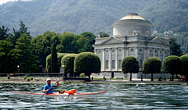 Photo of Kayaker on Lake Como paddling by an old building.