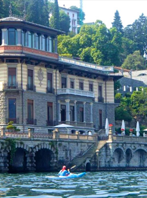Photo of kayaker on Lake Como with a villa in the background