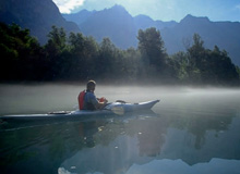 Photo of kayaker on Lake Como with mist on the lake